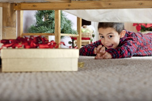 A young elementary boy delighted at seeing a boxed gift under his parents' bed.